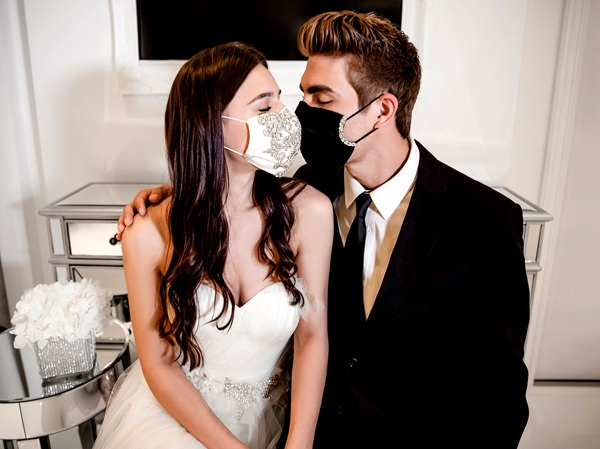 Bride and groom share kiss whilst wearing face masks, as post-Covid-19 wedding day landscape might offer new wedding photo editing opportunities.
