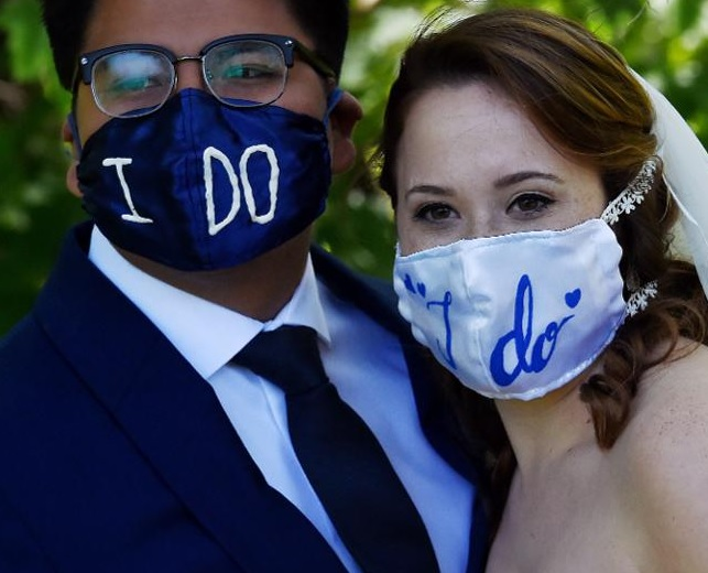 'I do' wedding face masks, as fashioned by bride and groom. Set to be commonplace sight at British weddings in the summer of 2020. meaning wedding photo editing companies could offer mask removal service.