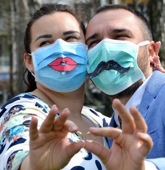 Newly-wed couple celebrate their wedding day, while wearing humorous Covid-secure face masks.
